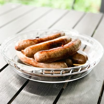 chicken sausages on a black table in glass plate